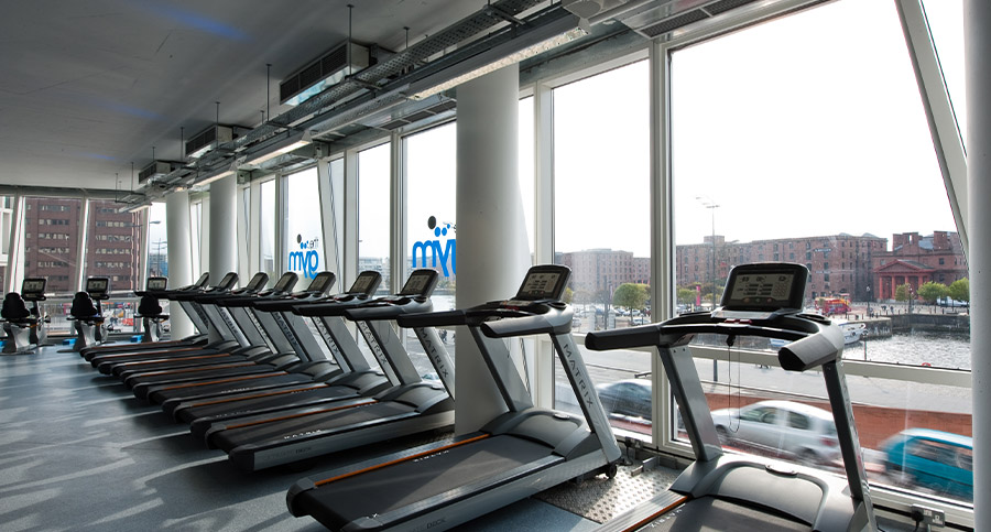 row of treadmills in a large gym design
