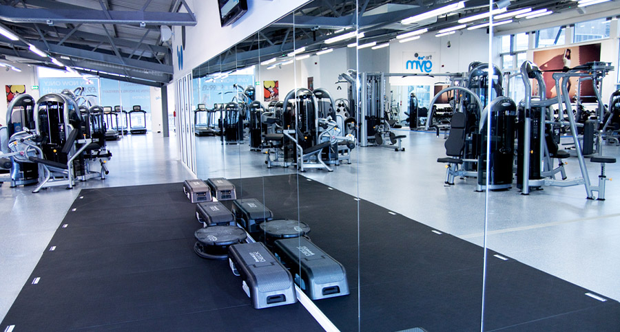 mirrors showing weights and equipment in a large gym