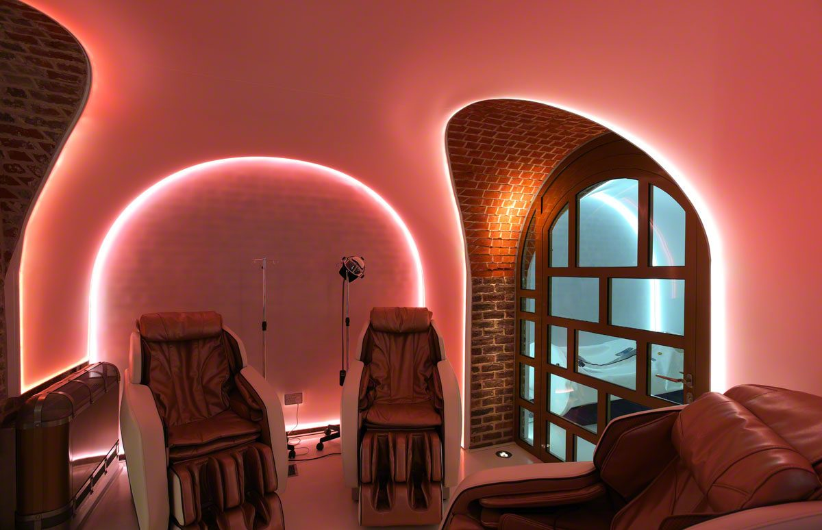 massage chairs in a red lit spa room